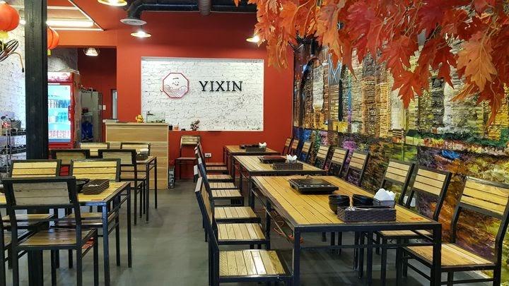 Tường tại nhà hàng được phủ hai màu đỏ - trắng làm nổi bật thương hiệu, kết hợp với những bộ bàn ghế đồng màu với vách tường ốp gỗ.